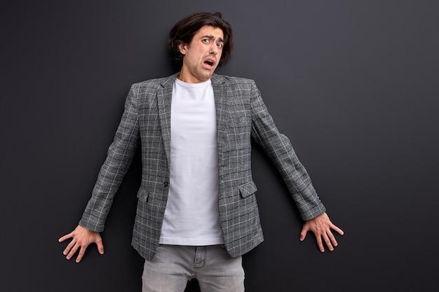 Un giovane spaventato è scioccato, spaventato da qualcosa, appoggiato al muro nero. il ragazzo caucasico in giacca e cravatta reagisce emotivamente a qualcosa,