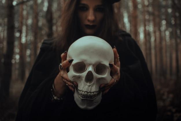 Una spaventosa strega malvagia vestita di stracci neri tiene tra le mani il teschio di un uomo morto per un oscuro rituale nella foresta