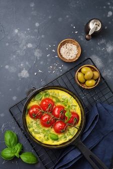 Frittata con rucola, patate e pomodorini in padella di ferro sul vecchio fondo della tavola in pietra.