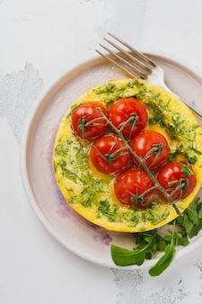 Frittata con rucola, patate e pomodorini in padella di ferro sul vecchio tavolo in pietra.