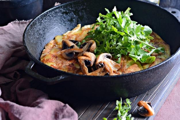 Frittata con patate, funghi, rucola ed erbe aromatiche per colazione su sfondo scuro.