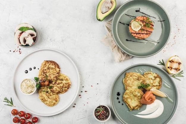 Frittelle a base di zucchine e insalata di avocado con salmone su piatti con il flusso dello chef su sfondo chiaro, vista dall'alto con copyspace. laici piatta. il concetto di colazione. cibo del ristorante.