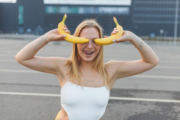 La giovane donna frivola e maliziosa con l'apparecchio sui denti che tiene le banane sul viso si diverte...