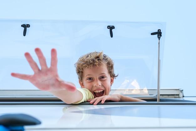 Dal basso ragazzo eccitato che sorride e raggiunge la telecamera mentre sbircia fuori dalla finestra del camper durante il viaggio su strada in una giornata senza nuvole