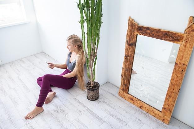 Dall'alto atleta femminile seduta sul pavimento vicino alla pianta in vaso e allo specchio e usa il telefono cellulare durante la pausa nell'allenamento fitness a casa