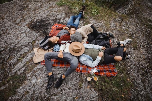 Dall'alto di un gruppo di viaggiatori maschi sdraiati su un plaid su un terreno roccioso mentre dormono nella natura