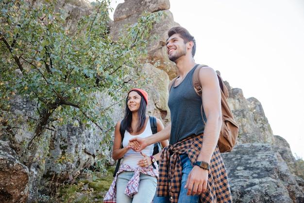 Da sotto l'immagine di giovani coppie felici che camminano sulla roccia