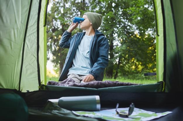 Dall'interno del colpo del ragazzo che guarda in un binocolo seduto in tenda durante il viaggio in campeggio nella foresta, copia dello spazio
