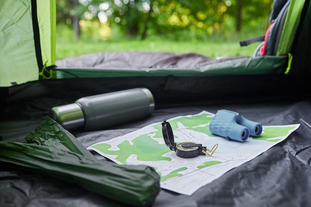 Dall'interno del colpo di tenda vuota con attrezzatura da campeggio, mcompass e mappa, copia dello spazio