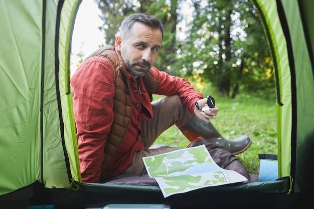 Dall'interno del colpo di uomo maturo seduto in tenda durante il viaggio in campeggio nella foresta, copia dello spazio