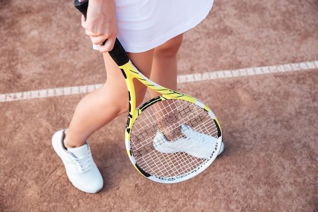 Da sopra le gambe del tennista in campo con la racchetta