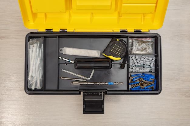 Dall'alto della scatola di plastica aperta con strumenti e accessori sul pavimento in legno