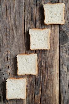 Dall'alto pezzi di mini toast contro il vecchio sfondo di legno