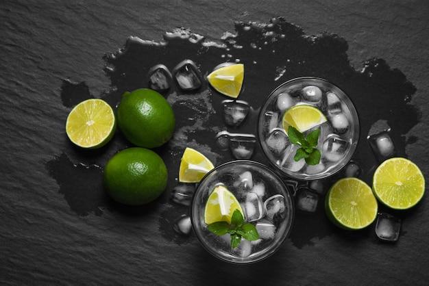 Dall'alto colpo di mojito alcolici e menta fresca con lime sul bancone di legno.