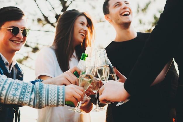 Dal basso inquadratura di giovani che ridono e tintinnano bicchieri di alcol con amici anonimi mentre festeggiano insieme nella natura