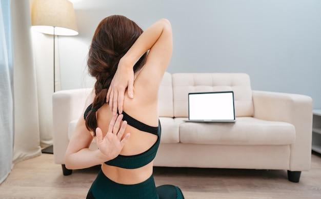 Da dietro sopra la spalla di una donna sportiva seduta sul pavimento e facendo stretching mentre guardi...