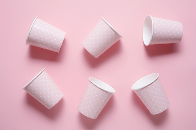 Da sei bicchieri di carta rosa su sfondi rosa