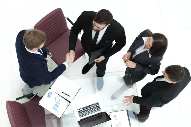 Dalla vista dall'alto stretta di mano dei partner finanziari alla riunione in ufficio