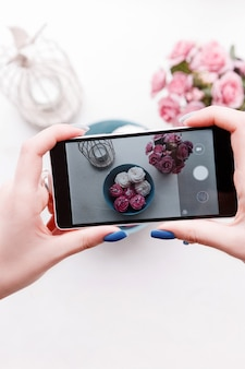 Dall'alto persona irriconoscibile che scatta foto di dolci e fiori con lo smartphone.