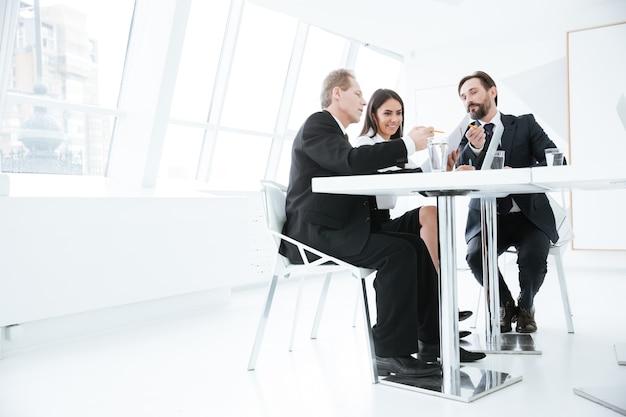 Dal basso vista del team aziendale seduto al tavolo in conferenza in ufficio