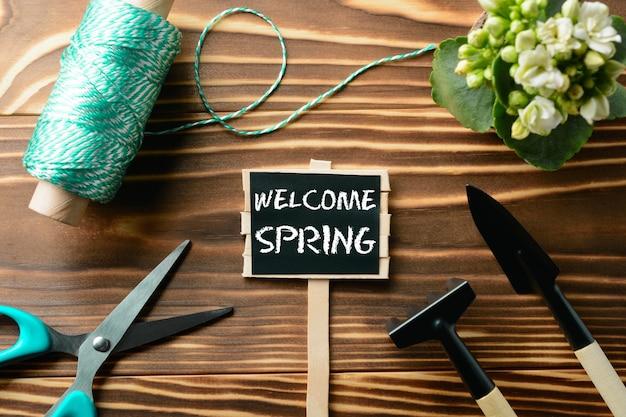 Dall'alto segno di benvenuto primavera e strumenti per il giardinaggio sulla tavola di legno