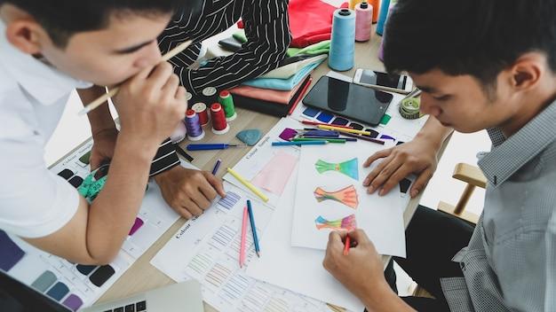 Dall'alto giovani uomini asiatici che si riuniscono intorno al tavolo e disegnano insieme uno schizzo di abiti eleganti mentre lavorano in uno studio su misura