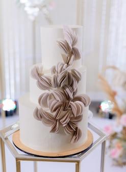 Vista ravvicinata frontale della bellissima torta nuziale minimalista in crema di colore bianco decorata con decorazioni di petali di rosa