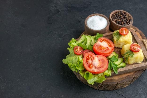 Vista frontale ravvicinata del formaggio di verdure fresche tritate e intere su tagliere e spezie sul lato sinistro su superficie nera