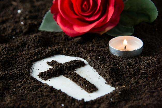 Vista frontale ravvicinata della forma della bara con la candela e il funerale del mietitore triste morte fiore rosso