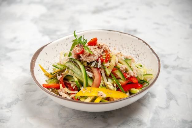 Vista frontale ravvicinata di deliziosa insalata di pollo con verdure su superficie bianca macchiata con spazio libero