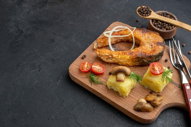 Vista frontale ravvicinata di deliziosi pesci fritti e funghi pomodori verdi su tagliere di legno posate pepe su superficie nera