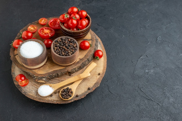 Vista frontale ravvicinata di pomodori freschi e spezie su tavola di legno su superficie nera con spazio libero