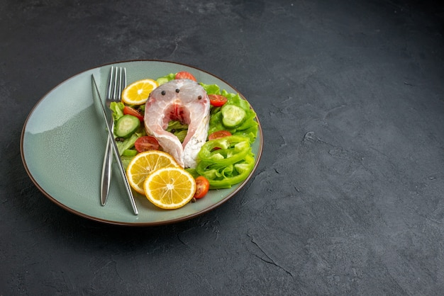 Vista frontale ravvicinata di pesce crudo e verdure fresche fette di limone e posate su un piatto grigio sul lato destro su superficie nera con spazio libero