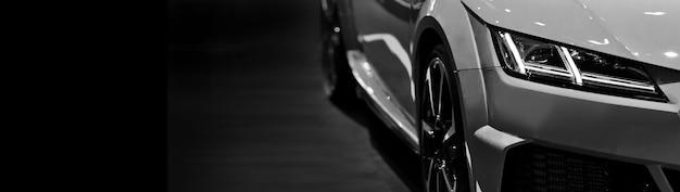 Fari anteriori della moderna auto sportiva in bianco e nero su sfondo nero spazio libero sul lato sinistro per il testo