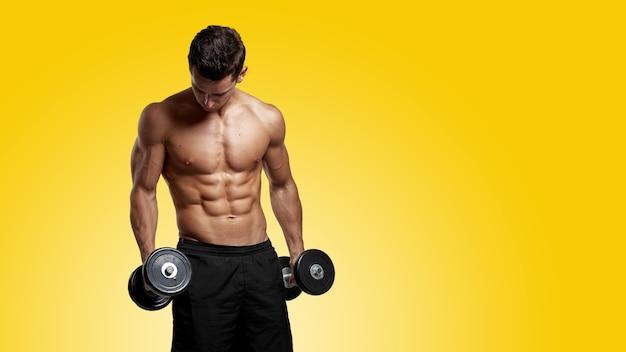 Immagine frontale di un giovane torso torso nudo in forma sicura che si allena con il dumb-bell, che mostra gli addominali scolpiti