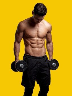 Immagine frontale di un giovane torso torso nudo fiducioso che si allena con il dumb-bell, mostrando sei pack abs