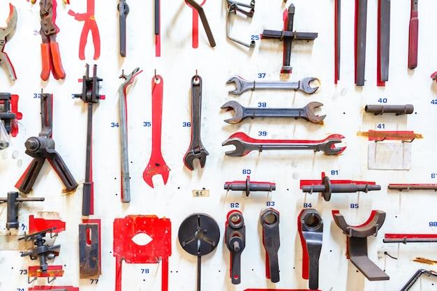 Parte anteriore degli strumenti di layout del tecnico su tavola di legno bianca. riparazione attrezzature e molti strumenti utili. kit di strumenti di riparazione.
