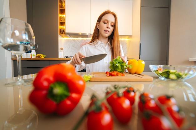 Vista frontale dal basso angolo di una giovane donna dai capelli rossi che taglia lattuga fresca che prepara insalata di cibo seduta a