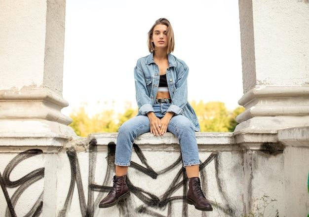 Ritratto frontale di una ragazza adolescente hipster, vestita in look denim e stivali, seduta fuori