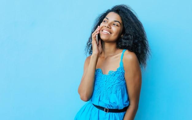 Ritratto frontale di una gioiosa ragazza afroamericana con capelli neri disordinati lunghi fino alle spalle, che ride sinceramente mentre parla al telefono e guarda a sinistra