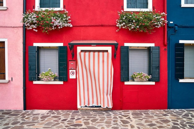 Davanti alla casa rossa decorata con fiori sulla famosa isola di burano. venezia, italia. viaggio