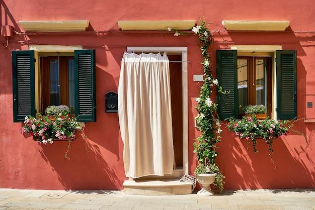 Davanti alla casa rossa con fiori sull'isola di burano. venezia, italia
