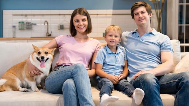 Famiglia adorabile di vista frontale che posa insieme al cane