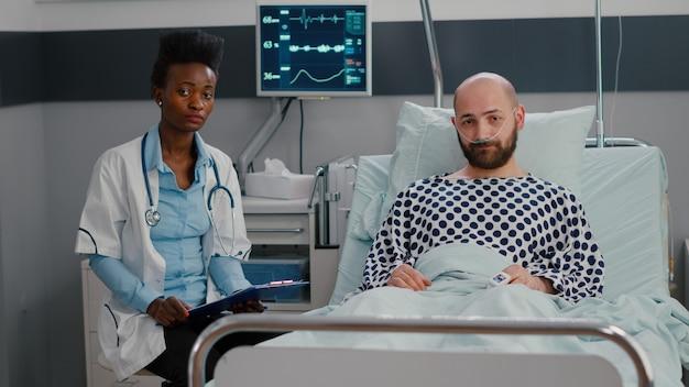 Vista frontale dello specialista medico afroamericano e dell'uomo malato che hanno una conferenza videochiamata online