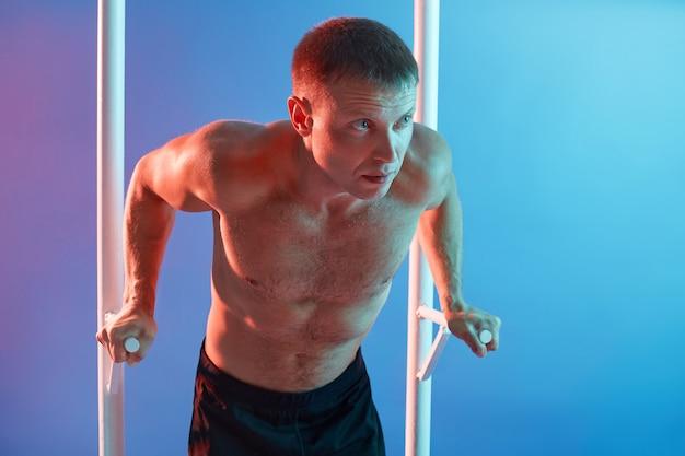 Vista frontale dell'uomo atletico che esercita allenamento calisthenics