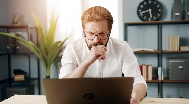 Vista frontale di un uomo d'affari maturo attento in camicia bianca e bicchieri lavorando sul computer in ufficio