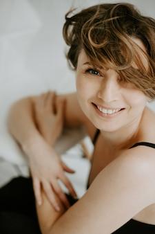 Vista frontale della donna castana attraente che sorride e che guarda l'obbiettivo