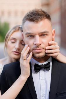 Vista frontale di sposini attraenti che guardano la telecamera