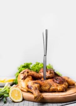Pollo intero cotto vista frontale sul tagliere con coltello e limone