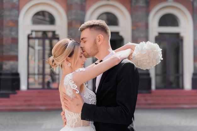 Vista frontale di bellissimi sposini che si abbracciano sull'edificio all'esterno dello sfondo